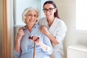 caregiver wearing glasses with an elderly woman